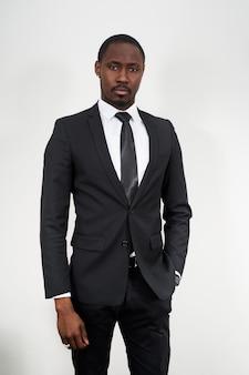 Ernsthafter afroamerikanischer geschäftsmann, der schwarzen anzug trägt