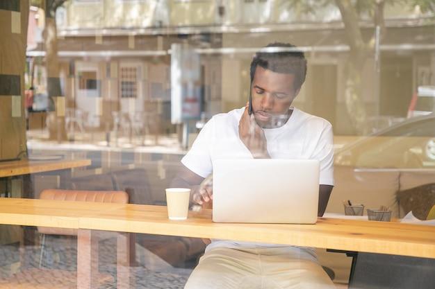 Ernsthafter afroamerikanischer mann, der auf laptop schreibt und auf handy im mitarbeitenden raum spricht