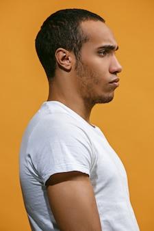Ernsthafter afroamerikanischer mann sieht ernsthaft gegen orange aus