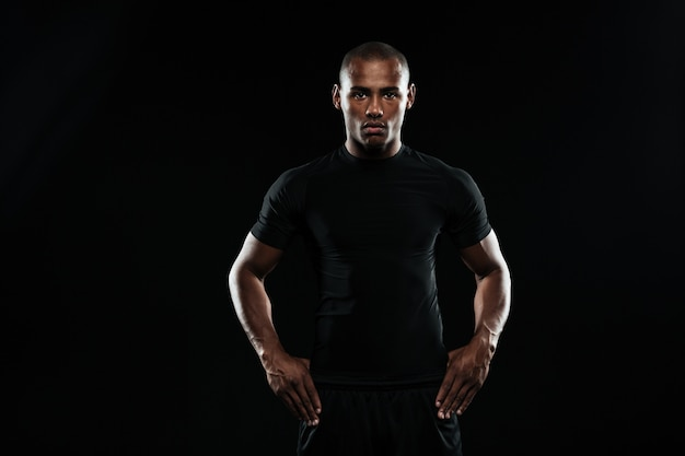 Ernsthafter afroamerikanischer sportmann mit armen auf seinen hüften, die kamera betrachten