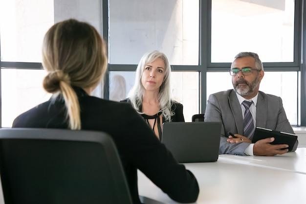 Ernsthafter arbeitgeber und personalmanager sprechen beim vorstellungsgespräch mit dem bewerber. rückansicht, nahaufnahme. personal- und karrierekonzept