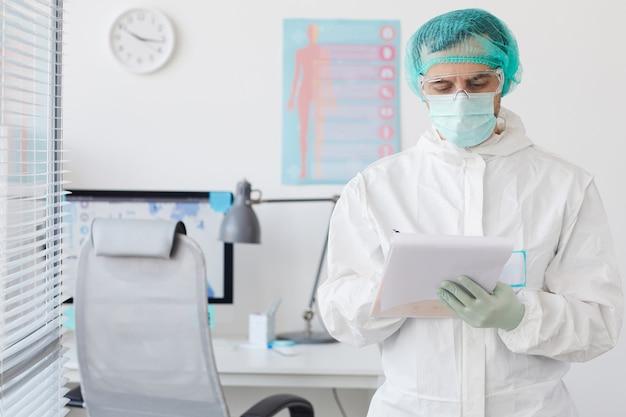 Ernsthafter arzt in schützender arbeitskleidung, die die medizinische karte füllt, während er im krankenhaus steht