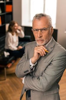 Ernsthafter arzt. taille eines gutaussehenden ruhigen kaukasischen psychotherapeuten, der in seinem büro steht und vor ihm schaut