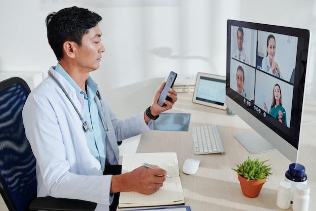 Ernsthafter asiatischer arzt mittleren alters, der eine online-konferenz mit kollegen hat und sich notizen im planer macht