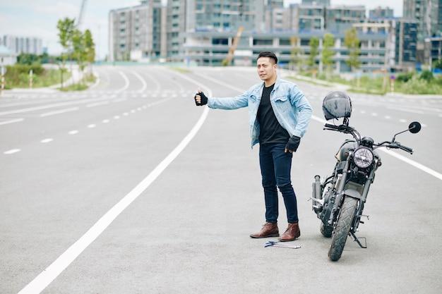 Ernsthafter asiatischer biker, der auto auf der straße fängt, als sein motorrad kaputt ist