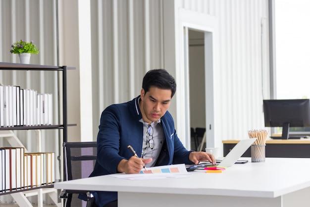 Ernsthafter asiatischer geschäftsmann, der notizen macht, mit papierdokumenten arbeitet, bericht am arbeitsplatz schreibt, fokussierter mitarbeiter, der wirtschaftsforschung mit laptop tut, männlicher student, der online-lernkurs studiert