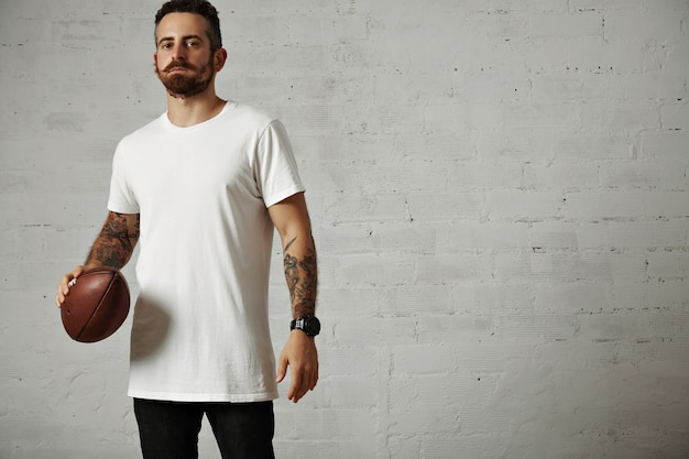 Ernsthafter attraktiver junger mann in einem leeren weißen baumwoll-t-shirt und in den schwarzen jeans, die einen vintagen rugbyball lokalisiert auf weiß halten