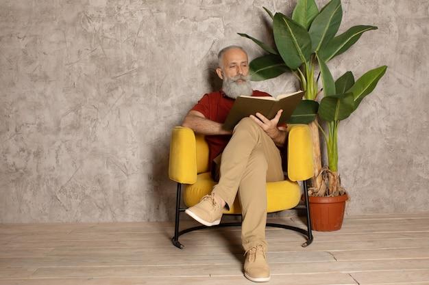 Ernsthafter bärtiger älterer mann, der interessantes buch liest, während auf gemütlichem sofa in der wohnung gelegen.