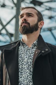 Ernsthafter bärtiger, gut gekleideter und gut aussehender geschäftsmann, der vor dem brückenbau beiseite schaut. nahaufnahmeporträt.