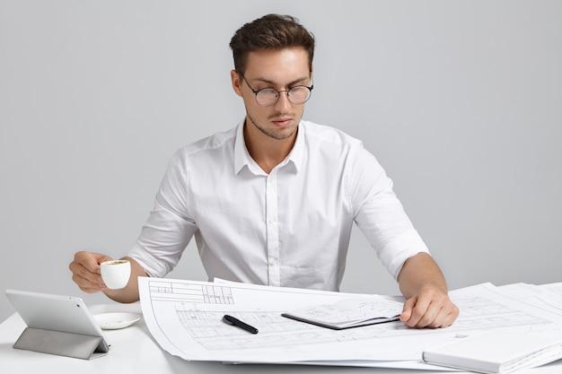 Ernsthafter beschäftigter männlicher designer, formell gekleidet, schaut aufmerksam in blaupausen, trinkt kaffee oder espresso.