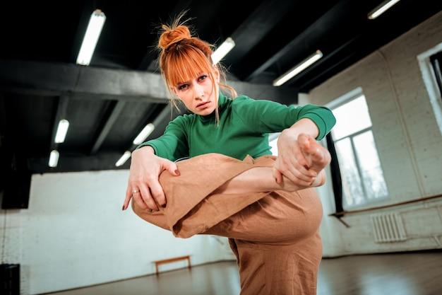 Ernsthafter blick. rothaarige professionelle choreografin mit haarknoten, die ernst aussieht, während sie ihre beine streckt