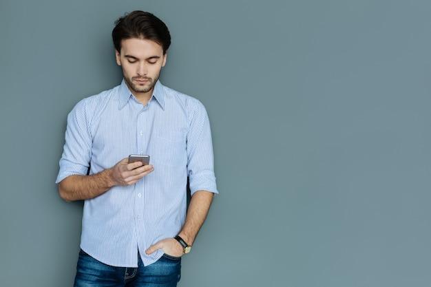 Ernsthafter blick. schlauer netter ernster mann, der steht und seine hand in eine tasche steckt, während er auf den smartphonebildschirm schaut