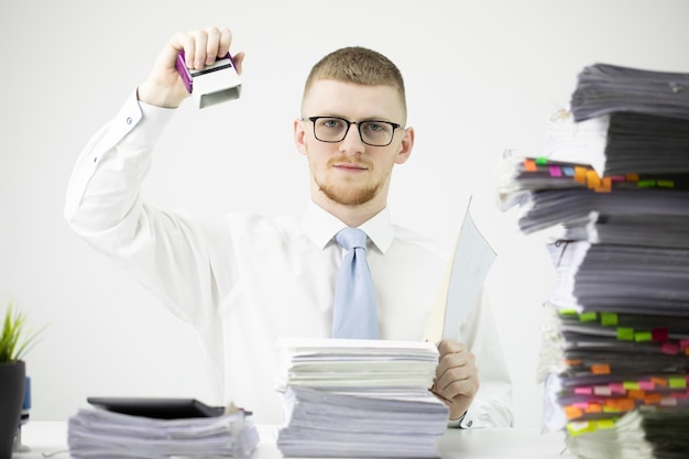 Ernsthafter büroangestellter im hemd mit krawatte und brille sitzt am tisch mit papierkram