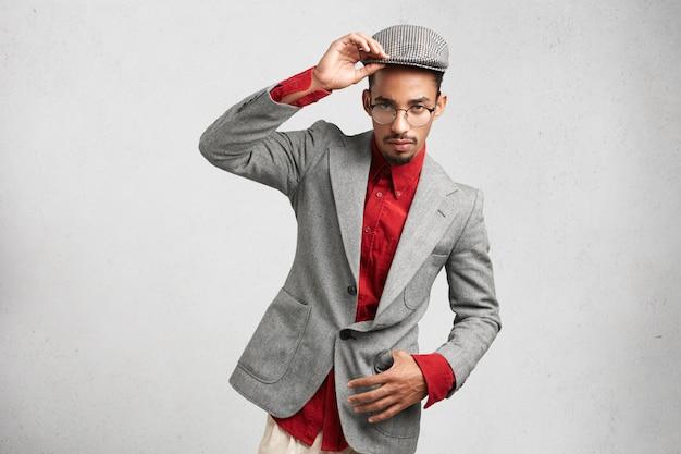 Ernsthafter dunkelhäutiger mann trägt formelle jacke und mütze, hat selbstbewussten ausdruck