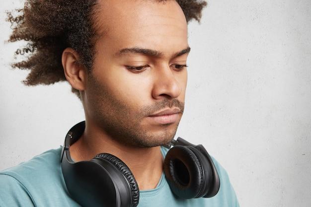 Ernsthafter dunkelhäutiger teenager mit buschiger frisur, hört musik mit kopfhörern