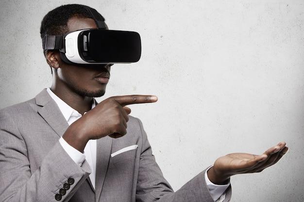 Ernsthafter dunkelhäutiger unternehmer im formellen anzug, der eine schutzbrille mit am kopf angebrachtem display für das smartphone trägt, gestikuliert, als ob er etwas auf seiner offenen handfläche hält und seinen finger auf den kopierraum zeigt