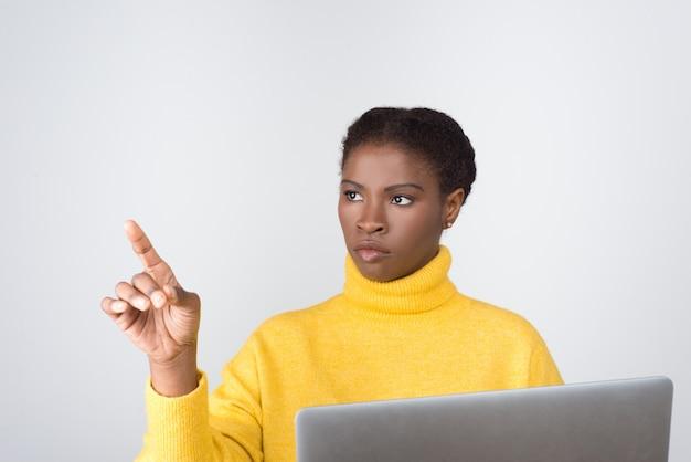 Ernsthafter entwickler, der laptop hält und virtuellen bildschirm berührt