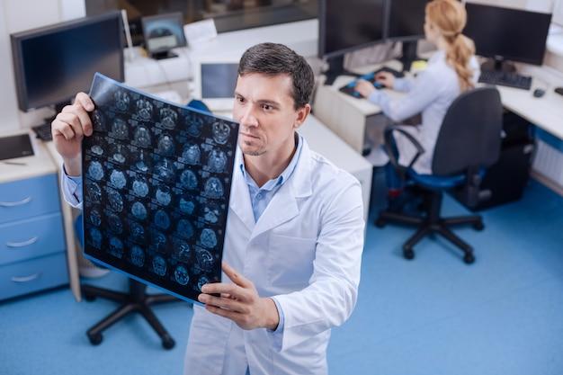 Ernsthafter erfahrener männlicher onkologe, der ein röntgenbild hält und es untersucht, während er im lehrerzimmer ist