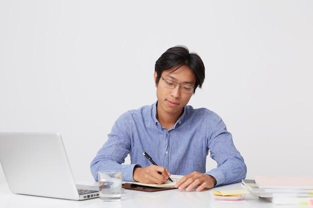Ernsthafter erfolgreicher asiatischer junger geschäftsmann in den gläsern, die mit laptop arbeiten und im notizbuch am tisch über weißer wand schreiben