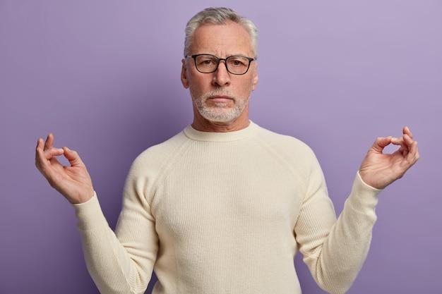 Ernsthafter faltiger alter mann meditiert drinnen, steht in yoga-pose, trägt eine optische brille, einen weißen pullover und versucht sich nach harter büroarbeit zu entspannen