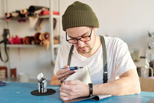 Ernsthafter fokussierter junger handwerker, der am schreibtisch sitzt und kante des leders in der werkstatt malt