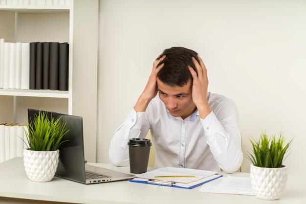 Ernsthafter frustrierter asiatischer geschäftsmann, der an kopfschmerzmigräne am arbeitsplatz leidet und sich müde, erschöpft, chronischen arbeitsstress fühlt