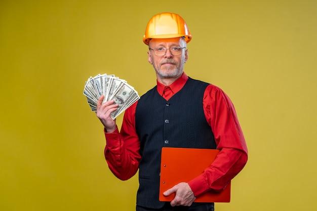 Ernsthafter generalunternehmer oder immobilieninvestor beim bau eines helms mit dollars