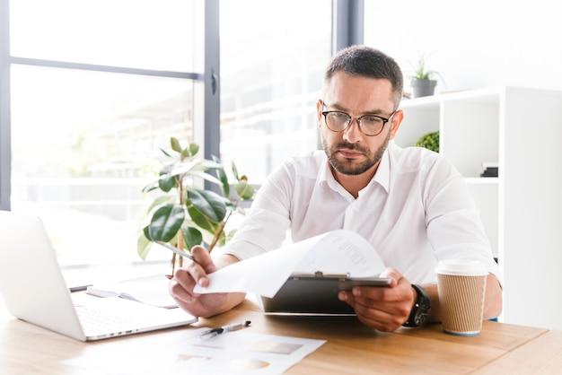 Ernsthafter geschäftsmann 30s im weißen hemd, das papierdokumente während der arbeit im büro hält und prüft