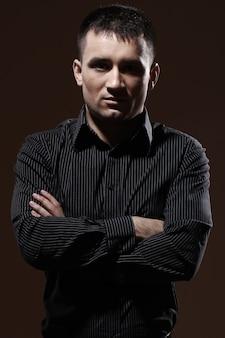 Ernsthafter geschäftsmann mit gestreiftem schwarzem t-shirt und schwarzen hosenpantalones