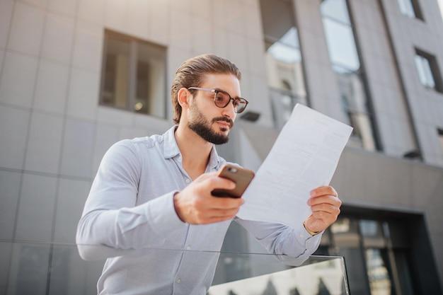 Ernsthafter geschäftsmann steht auf und betrachtet ein stück papier durch eine brille. er ist ruhig und friedlich. junger mann hält telefon in rechter hand.