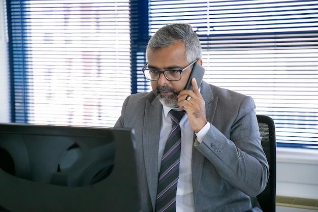 Ernsthafter grauhaariger geschäftsprofi im anzug, der auf handy spricht, während er computer am arbeitsplatz im büro benutzt. mittlerer schuss. digitales kommunikations- und multitasking-konzept