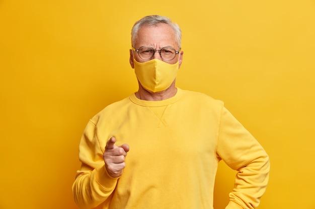 Ernsthafter grauhaariger mann schaut mit striktem ausdruck an den vorderen punkten zeigefinger nach vorne und gelbe gesichtsmaske, während der schutz vor viren in innenräumen steht