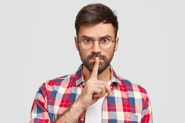 Ernsthafter gutaussehender mann fordert völlige stille, macht leise geste