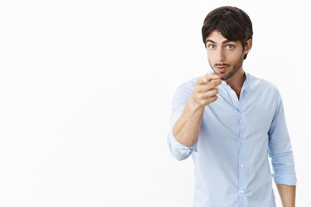 Ernsthafter herrischer und unzufriedener attraktiver männlicher unternehmer im hemd, der nach vorne zeigt, da er unzufrieden mit unproduktiver arbeit ist und den mitarbeiter warnt, dass er gefeuert werden könnte