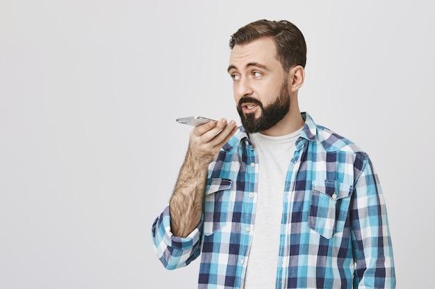 Ernsthafter hübscher bärtiger mann zeichnet sprachnachricht mit lautsprechertelefon auf