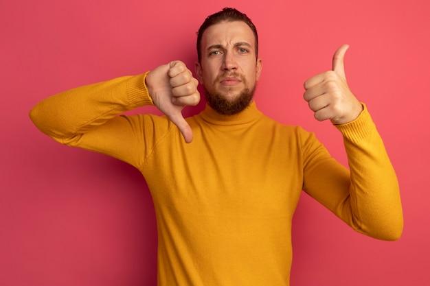 Ernsthafter hübscher blonder mann daumen hoch und daumen runter auf rosa