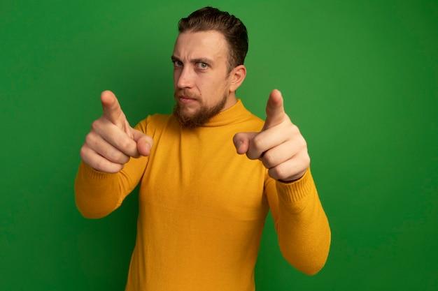 Ernsthafter hübscher blonder mann zeigt nach vorne mit zwei händen, die auf grüner wand lokalisiert werden