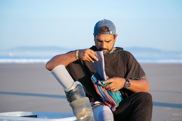 Ernsthafter hübscher junger mann, der am strand sitzt und prothese unter dem knie anlegt