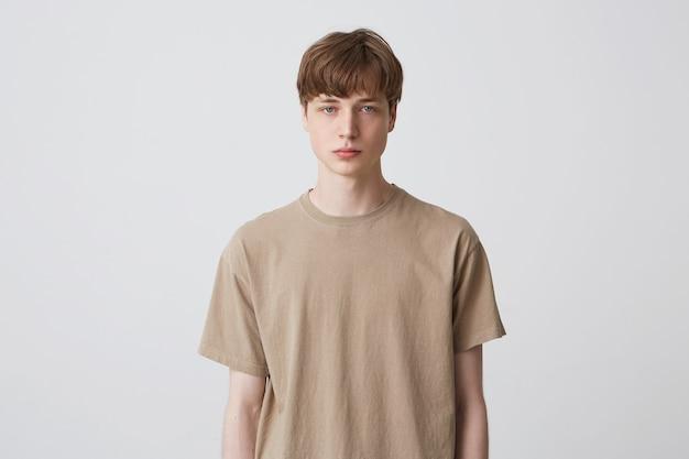 Ernsthafter hübscher junger mannstudent mit kurzem haarschnitt und blondem haar