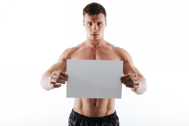Ernsthafter hübscher junger sportler, der copyspace-papier hält