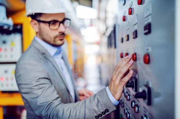 Ernsthafter hübscher kaukasischer aufseher im grauen anzug und mit dem helm auf kopf, der schalter einschaltet. selektiver fokus zur hand. kraftwerksinnenraum.