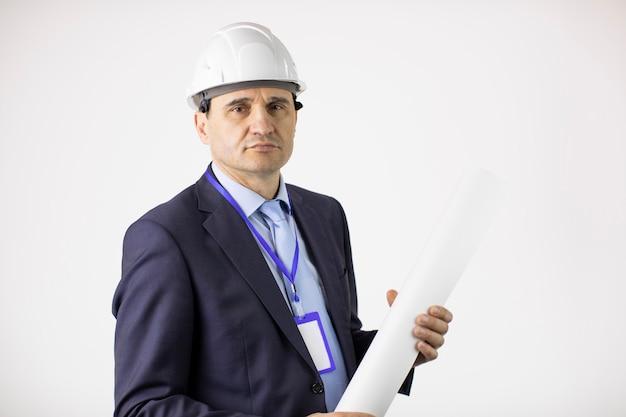 Ernsthafter ingenieur im schutzhelm schaut zuversichtlich auf kamera, die blaupausenrolle hält