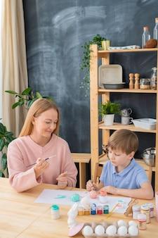 Ernsthafter junge, der am tisch mit papieren sitzt und eier malt, während osternentwurf mit mutter erstellt