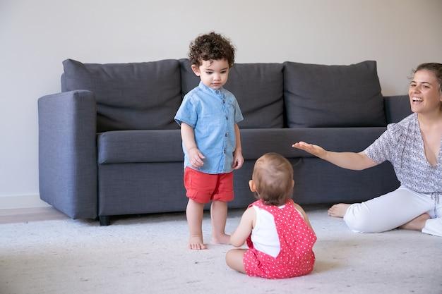 Ernsthafter junge mit gemischten rennen, der steht und baby ansieht. kaukasische hübsche mutter, die etwas mit kindern spricht, lächelt und mit kindern zu hause spielt. familienhaus, wochenend- und kindheitskonzept