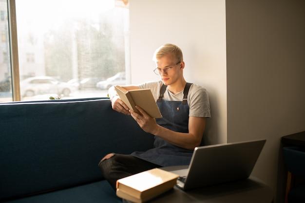 Ernsthafter junger arbeiter der cafeteria, der am fenster sitzt, während er bücher über modernen service und restaurantgeschäft liest