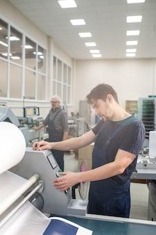 Ernsthafter junger arbeiter in der gesamtstellung an der druckmaschine und auswahl der kopienmenge auf dem bedienfeld