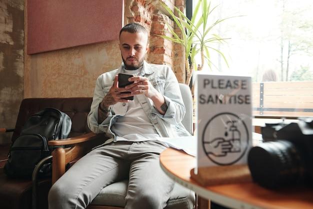 Ernsthafter junger bärtiger mann, der im café sitzt und netz auf smartphone surft, während auf bestellung zum mitnehmen wartet