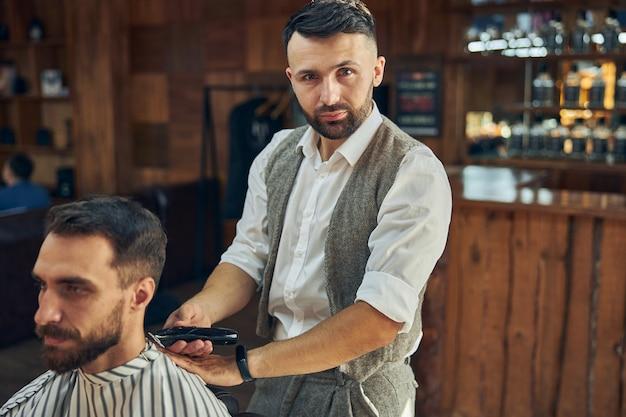 Ernsthafter junger friseur, der professionell aussieht, während er seinem kunden in einem friseursalon einen frischen haarschnitt gibt