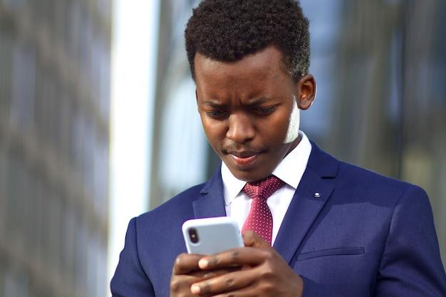 Ernsthafter junger geschäftsmann im formellen anzug, der bildschirm seines handys ansieht. schwarzafrikanischer afroamerikanischer mann, der eine nachricht auf smartphone im freien, stirnrunzeln tippt.
