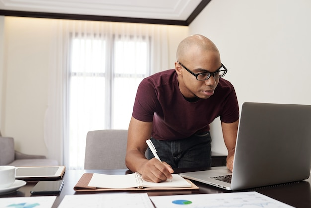 Ernsthafter junger geschäftsmann in der brille, der e-mails oder berichte auf laptop-bildschirm überprüft und notizen im planer macht